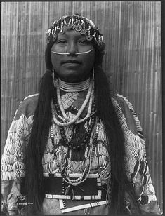 1910 Edward S. Curtis photo of a Tlakluit woman, wearing a heavily beaded buckskin dress, several necklaces, beads, shells, dentalium-shell nose ornament and a headdress of beads and hollow-centered Chinese coins.  Entitled: Wishham (i.e., Wishram) girl