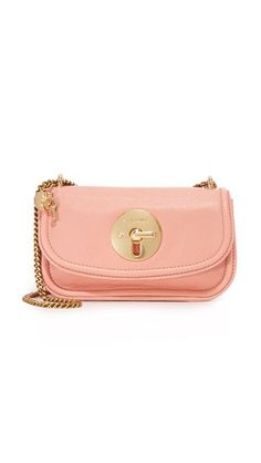 A tiny See by Chloé cross-body bag crafted in buttery leather. A logo-embossed turn-lock clasp fastens the flap.