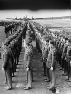 Men of the 8th Air Force standing at attention during an award ceremony for the Distinguished Flying Cross. (September 1942)