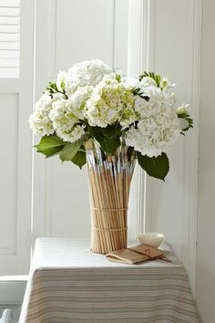 """Blogger Camilla Fabbri gives used paintbrushes a new lease on life with this fanciful centerpiece. """"I love the way the colorful bristles look,"""" says Fabbri, an Evanston, Illinois, artist, """"and the whole thing takes just minutes."""" Simply space two rows of plain rubber bands around a tall, cylindrical vase, then tuck brushes (Fabbri used about 40) inside the bands until the tools completely surround the vessel."""