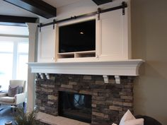 sliding doors over tv above fireplace