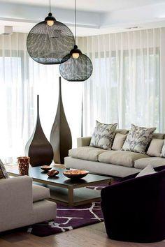 salon élégant avec canapé rembourré en gris clair, tapis pourpre, table basse en bois et suspensions boules