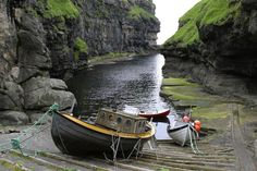 Boats at natural harbor at Gjogv, Faroe Islands. The Faroe Islands are an island group situated between the Norwegian Sea & North Atlantic Ocean, halfway between Scotland and Iceland.