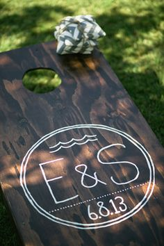Cornhole boards at wedding reception with bride and grooms initials and married date. So cute!