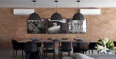 Neste apartamento de 270m² com referências de decoração dos lofts nova iorquinos industriais, a sala de jantar conta com um mix de cadeiras pretas e mesa em laca cinza brilhante. Três quadros preto e branco, do artista Rodrigo Petrella, fazem uma composição urbana na parede.