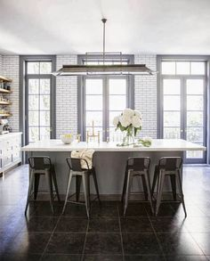 The kitchen in a West Village apartment with garden views.  A city apartment kitchen with a sophisticated country look.  Subway tile with dark grout line the walls, dark charcoal gray cabinets and gray trim around the large french doors, brass accents adding a bit of gleam and white marble counters. COCOCOZY
