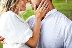 casal se beijando e mostrando a aliança de noivados com a mão