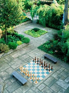 In this spacious outdoor area, made up of several interconnected slate patios, a chessboard with oversized pieces has been erected between two benches. Ornamental grass, shrubbery, and trees border each of the individual spaces for a well-manicured appearance.