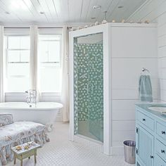I love the corner shower and the colourful tiles, also LOVE the tub, love the white wood, feels like a comfy holiday  home    Blue dresser as vanity with shell-patterned upholstery on a chaise lounge in bathroom with claw-footed tub and stand-shower stall