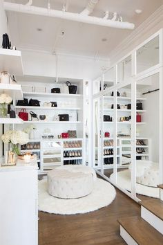 This large, white, glam walk-in closet boasts exposed ductwork fitted above a round white tufted ottoman placed on a round white faux fur rug in front of mirrored wardrobe cabinets. Dressing Room Closet, Dressing Room Design, Walking Closet, Wardrobe Room, Wardrobe Cabinets, Wardrobe Storage, Walk In Wardrobe, Closet Storage, Loft Closet