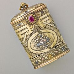 FOUR COLOR GOLD AND RUBY POMANDER CASE. Oval pierced and chased in the Louis style with colored gold and silver applique, Hinged lid with bail, ruby thumbpress, ca. 1800.