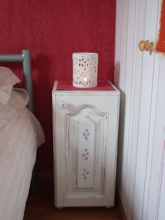An old kitchen wall cupboard got the shabby chic treatment to transform it into a bedside cabinet. The legs are wooden door knobs and the rose design is decoupage...