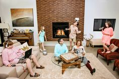 A family of six poses in their living room, each participating in their favorite pastimes.