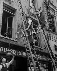 """historicaltimes: """" Shopkeeper removing the word, 'Italian' from the sign above…"""