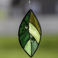 This beautiful stained glass multicolor green leaf suncatcher is made of hand cut glass. The pieces are individually wrapped in copper foil and soldered together. It comes ready to hang with a sturdy hook and clear line. It measures approximately 3 x 6 1/2 inches (stem adds an additional 1 inch). The stem is handcrafted from copper tinned wire. It is framed in lead came. The solder is waxed and buffed to shine. There are 2 glass jewels to add depth and detail. This suncatcher will look g...