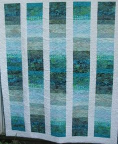 Batik quilt ... teals, blues and greens surrounded by a border of white.