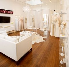Bridal shop with all white décor, neon sign, and hanging dresses