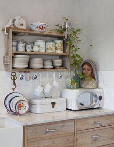 תצוגת כלי אוכל מרהיבה בפינת האוכל, מראה קלאסית מעל הכיור במטבח, עיטורי זהב על הקיר בסלון וספריית ארגזים ייחודית בפינת העבודה. הביתה של קרן שביט בקיבוץ גבת, חלק א'