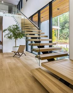 Staircase, Wood Tread, and Glass Railing Set on top of a forested ridge separating downtown Portland and the suburban sprawl of Beaverton, OR, Wildwood by Giulietti / Schouten AIA Architects is a rural retreat and primary residence hidden within th
