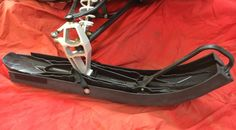 Ski-Boot installed on a snowmobile showing how the tip of ski locks into boot with strap securely fastening around back of spindle.