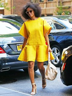 Solange Knowles in a yellow drop waist dress, nude sandals, and cat-eye sunglasses
