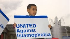 A boy holds up a placard reading