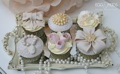 Pretty vintage cupcakes with handmade bows, rose buds and brooches