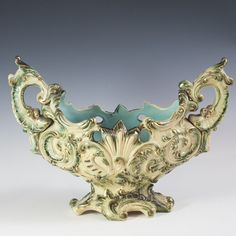 "DESCRIPTION:Majolica ceramic centerpiece by Wilhelm Schiller & Son. Features ornate rococo style embossed designs along the body and arching side handles. Finished with gilded trim and olive green polish. Marked:""WS&S"" along with serial numbers. CIRCA:19th-Early 20th Ct. ORIGIN:Austria DIMENSIONS:H:10"" L:13.5"" W:5.75"""