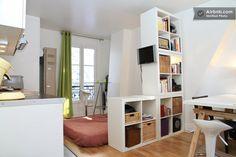Clever use of shelves as a divider between bedroom and living space in a studio flat