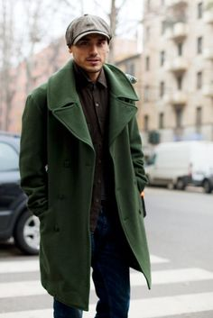 Dress in a green overcoat and navy jeans if you're going for a neat, stylish look.  Shop this look for $2,133:  http://lookastic.com/men/looks/grey-flat-cap-black-longsleeve-shirt-green-overcoat-navy-jeans/4383  — Grey Flat Cap  — Black Longsleeve Shirt  — Green Overcoat  — Navy Jeans