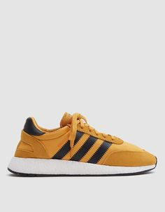 Adidas-Iniki Boost in Tactile Yellow Revamped take on a 70's runner from Adidas in Yellow. Two-way stretch mesh and vintage suede upper. Lace-up front with flat woven laces. Hidden sock construction. Lightly padded collar. Deconstructed heel cap. Printed serrated '3-Stripes' branding at lateral and medial sides. OrthoLite®️️️ sockliner. Adidas branding throughout.