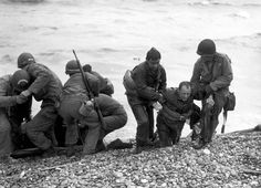 Members of an American landing party help others whose landing craft was sunk by enemy action off the coast of France. These survivors reached Omaha Beach by using a life raft on June 6, 1944.