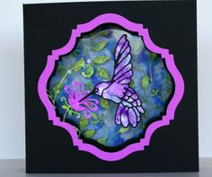 A 4 layer shadow box card with an alcohol ink bird, leaves and background and a Go Kreate die frame.