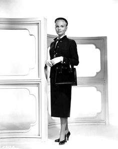A working girl habit. Eva Marie Saint wears a two-piece charcoal gray wool suit with very straight button-to-the-neck jacket and a pencil slim skirt. A small velveteen collar decorates the jacket with brass buttons at sleeves and front. A crisp white blouse with black ribbon tie, black beret, and matching kid bag and shoes add the touch of a well-groomed secretary