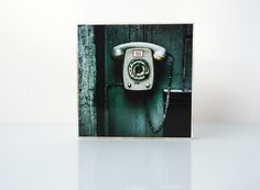 Motiv: Telefon  Das Foto wurde auf eine weißgestrichene Holzplatte gezogen.  Jedes Stück ist in eigener Handarbeit entstanden. Kleine Unregelmäßigkeiten sind gewollt und machen dieses Bild zu...