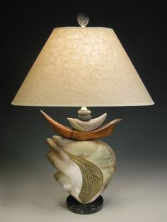 Feather Light by Jan Jacque. Birds interpreted through the artist's eyes create this unexpected balance of ceramic and walnut wood. A combination of variegated colored glaze on the textured inset and the unique flashing of the pit firing provides the beautiful surfaces on this sculptural lamp. It comes with an oval vanilla crepe paper lampshade with spider assembly and attaches to harp with a unique clay stone finial. 3 way switch, 150 watt maximum (bulb not included). Dimensions include…