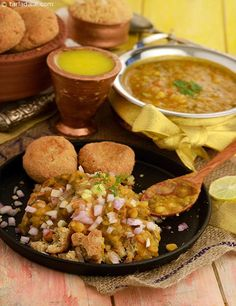 Dal Baati Churma consists of baatis or flaky round breads served dipped in ghee accompanied with panchmel or panch kutti dal and churma.