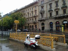 A small scooter parked along the entrance to a subway station on Andrassy Utca in Budapest, Hungary on a rainy autumn day.