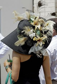 A spectator walks through the paddock with her fancy hat before the 138th Kentucky Derby horse race at Churchill Downs Saturday, May 5, 2012, in Louisville, Ky