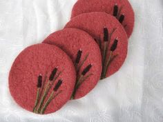 Coral color wool felted coasters with needle felted Cat Tails design