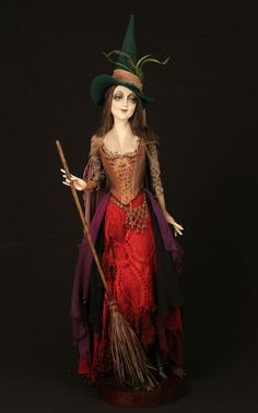 Gabriella, by Dustin Poche'  This pretty little witch is getting the house ready for All Hallow's Eve. Gabriella wears a pin striped corset with embroidered floral stomacher, a red tatted lace top skirt, paired with silk chiffon underskirts in shades of scarlet and eggplant, topped with a perky pointed green wool hat.  37 INCHES (93.98 CM) TALL  Paper Mache, wood, stain, acrylic paint, chalk powder, wire, Alpaca fiber, wool, embroidery, straw, tatting.