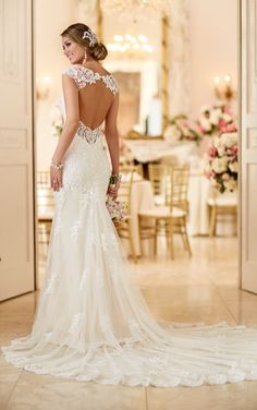 This lace over matte-side Lustre satin wedding gown from Stella York features hand-sewn clear beading, a sweetheart neckline with deep V detailing, cap sleeves, and a keyhole back with an easy-close back zipper and layered train.