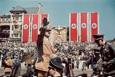 Brutal Pageantry: Adolf Hitler salutes troops of the Condor Legion who fought alongside Spanish Nationalists in the Spanish Civil War during a rally upon their return to Germany, photographed in color by Hugo Jaeger (1939)