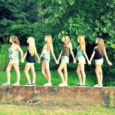 Group of friends pose on concrete wall. Best friends photo shoot.
