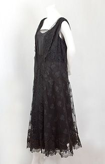 Mixed lace dress, early 1920s. The alluring dress recapitulates Spanish fashion history, where black lace has intimated romance and mystery for 400 years. The two layers are attached at the neckline and armholes. The flared outer layer of black Chantilly lace, black tulle, and embroidered cutwork floats over a straight black satin slip. The black-on-black design enhances the rich complexity of the intricate floral lace motifs.