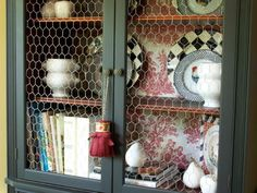 chicken wire open cabinet door, red toile backing, exposed dishes & cookbooks