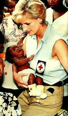 January 14, 1997: Diana, Princess of Wales comforts a baby at a Red Cross Health Center in Luanda, Angola.