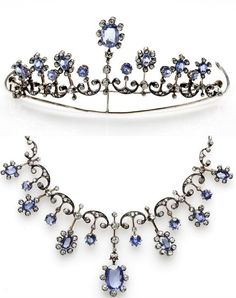 An early 20th century sapphire and diamond necklace/tiara. The front piece is of graduated fringe design, formed as seven diamond-set knife edge bars each terminating in an oval-cut sapphire surrounded by old round brilliant-cut diamonds and spaced by a scrolling diamond-set link each with a knife edge bar drop terminating in a circular-cut sapphire, to a belcher-link neckchain, mounted in silver and gold, with a tiara frame, length 42cm including chain