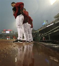 Boston Red Sox manager John Farrell pauses during the national anthem as rain collects in front of the dugout before a baseball game against the Cleveland Indians at Fenway Park in Boston, Friday, May 24, 2013. (AP Photo/Charles Krupa)