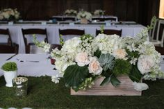 Natural, rustic wedding centerpiece of flowers, foliage and succulents: white hydrangea, peach carnations, peach juliet garden roses, larkspur, queen anne's lace, green trick dianthus by www.redpoppyfloral.com at Cottonwood Barn